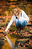 Woman next to stream in autumnal forest
