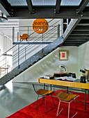 Schreibtisch mit Stühlen im 60er Jahre Stil in offenem Wohnraum unter Galerie mit Treppe aus Stahl