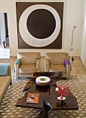 Hand-made, artistic coffee table and modern, sand-coloured sofa set in front of modern painting on wall