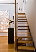 Staircase with wooden treads in open-plan foyer and objet d'art on pedestal and mounted on wall