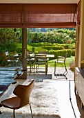 Interior with seating area on flokati rug in front of open terrace door with view of table and chairs in sunny garden