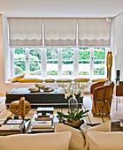 Couchtisch, mexikanischer Sessel, Ledersofa und Sitzkissen auf der Fensterbank in einem Wohnzimmer