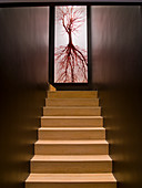 Light wooden staircase, dark walls and photo poster in stairwell
