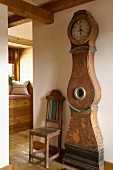Antique grandfather clock with curved case and an old wooden chair in a renovated, rustic old building