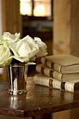 weiße Rosen in Silberbecher und historische Bücher auf alter Tischplatte
