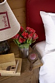 Bouquet of tulips, carved hand mirror and plushy lamp shade on a rustic, antique night table