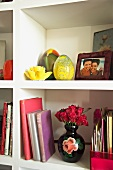 White book shelves with vase of roses, yellow glass eggs and framed family photos
