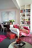XXXL chair in front of bookshelves and modern art above an old writing table -- living room with red and pink carpets and accessories