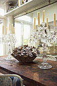 Crystal candelabras and small basket filled with floral decorations on an old wooden talbe