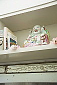 Laughing, Buddha made of Chinese porcelain next to books in a bookshelf
