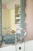 Bathtub fitting in retrostyle in front of an antique mirror with carved, blue pastel frame