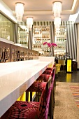 Bar stools with purple floral upholstery at counter in foyer with black and white striped wallpaper