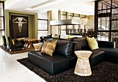 Modern, open living room with black leather sofas and chairs and ethnic South African elements