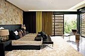 Modern bedroom with animal skin and leather; lounger in front of large, open sliding louvered doors