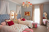 Romantic bedroom with single beds and a chest of drawers with a mirror between them; pink accents create a warm and cheerful atmosphere