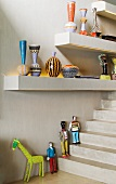 Painted vases on shelves with integrated lights and painted figures on the steps