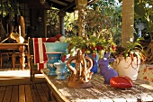 Sunny wooden terrace with vintage table, flowers and colorful decorative objects