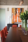 Long dining table with a purple bouquets in glass vases and modern art on the wall