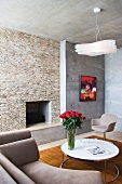 Corner sitting with designer furniture in front of a fireplace clad in natural stone and raw exposed concrete walls