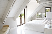 Elegant, antique-style furniture in white bedroom under exposed roof structure of modern country house