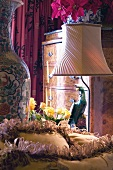 Detail of boudoir - lamp next to colourful parrot figurine and Baroque chest of drawers