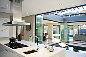 A white kitchen counter with an extractor fan and a view over an open courtyard with a pool and an adjoining living room-cum-dining room