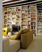 Seating area in modern, Italian design in front of large, white bookcase acting as partition
