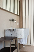 Modern stone sink with wall-mounted taps and side table in corner of bathroom