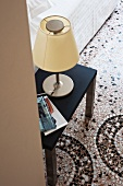 Table lamp with yellow fabric lampshade on side table on terrazzo floor