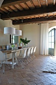 Dining area with white shell chairs on old terracotta floor in renovated country house