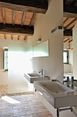 Designer bathroom in renovated country house - two sinks with mirrors and glass shower partition