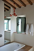Designer bathroom with red lacquered chandelier hanging from wooden beams of ceiling in renovated country house