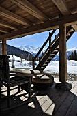 Terrassenplatz vor Holzhütte in verschneiter Berglandschaft