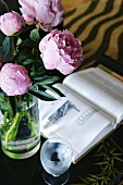 Glass vase with pink peonies next to open book and glass of water