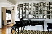 Concert grand piano against wall with gallery of pictures in open-plan music room