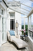 Art Deco-style chaise longue with white upholstery in conservatory