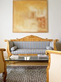 A Biedermeier-style sofa with striped upholstery and a modern, glass-topped coffee table