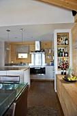 Offene Designerküche mit teilweise holzverkleideten Wänden