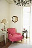Antique armchair with ornamental pattern on pink brocade upholstery in corner of traditional room