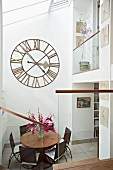 View of dining area beneath antique wall clock in glass-roofed anteroom