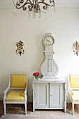 Baroque armchairs with yellow covers next to white-painted longcase clock on cabinet