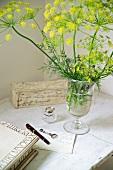 Flowering stalks in glass vase on table