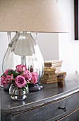 Posy of roses in glass vase in front of table lamp with mirrored base and fabric lampshade