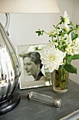 White flowers in glass vase next to framed photograph