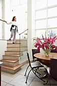 Woman walking down stairs in light foyer with dining area