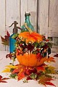 Autumn arrangement of colourful leaves, pumpkin and garden flowers