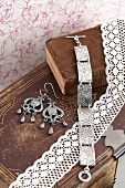 Silver bracelet with floral pattern and drop earrings on old leather bound books