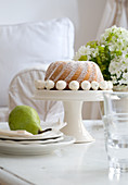 Decorated bundt cake on cake stand and pear on plates