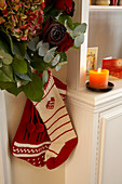 Knitted Christmas stockings hanging below flower arrangement with roses and hydrangeas and next to lit candle on living room cabinet