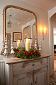 Hall mirror above candle in arrangement of roses and stylised metal fir trees on vintage cabinet